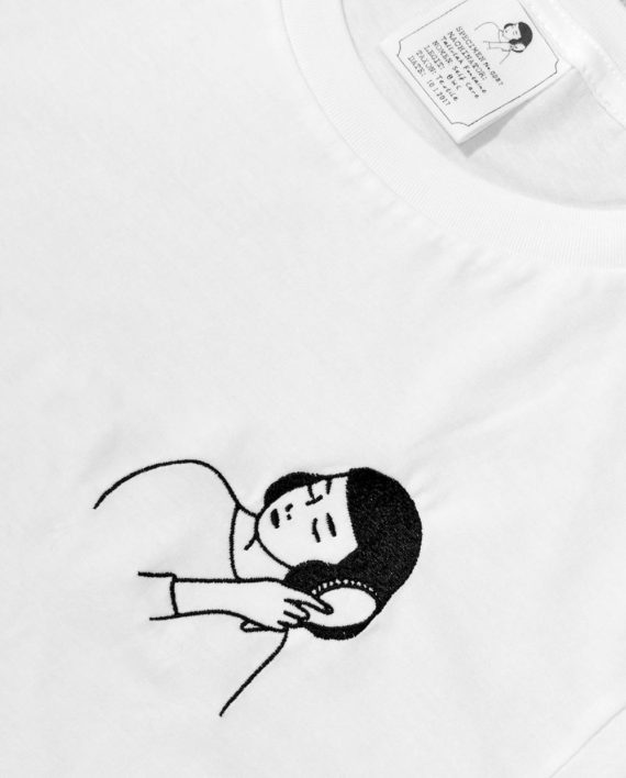 Self Care embroidery of girl brushing her hair in black. Embroidery on white t shirt.